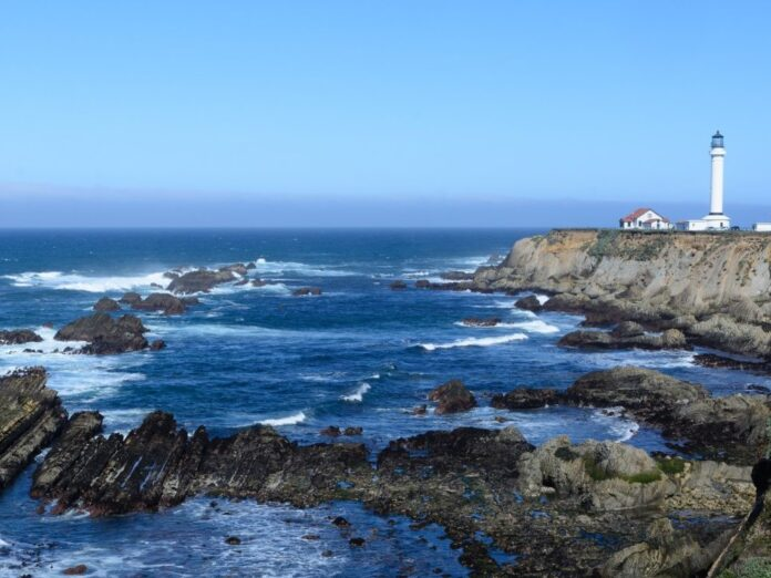 Point areana lighthouse california landscape with blue waters and blue skys. The lighthouse is right on a cliff.