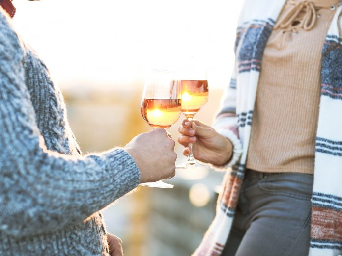Man and woman with wineglasses outdoors- A Taste of Redwood Valley