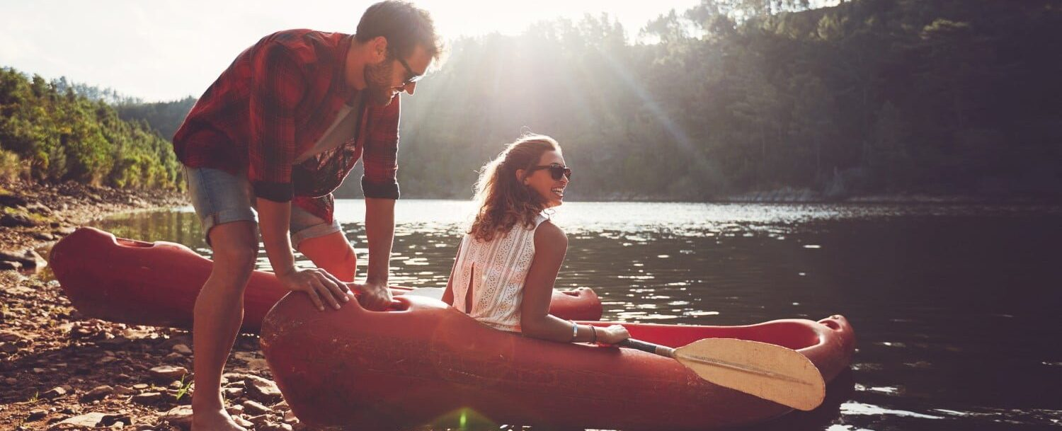 Couple launching on a canoe on the rivershore with rental company Catch a Canoe & Bicycles, Too