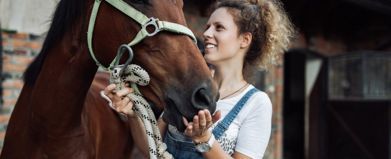 Woman posing with horse at a stable - Ridgewood Ranch