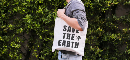 Man carrying a save the earth bag during his eco-friendly travels to Mendocino
